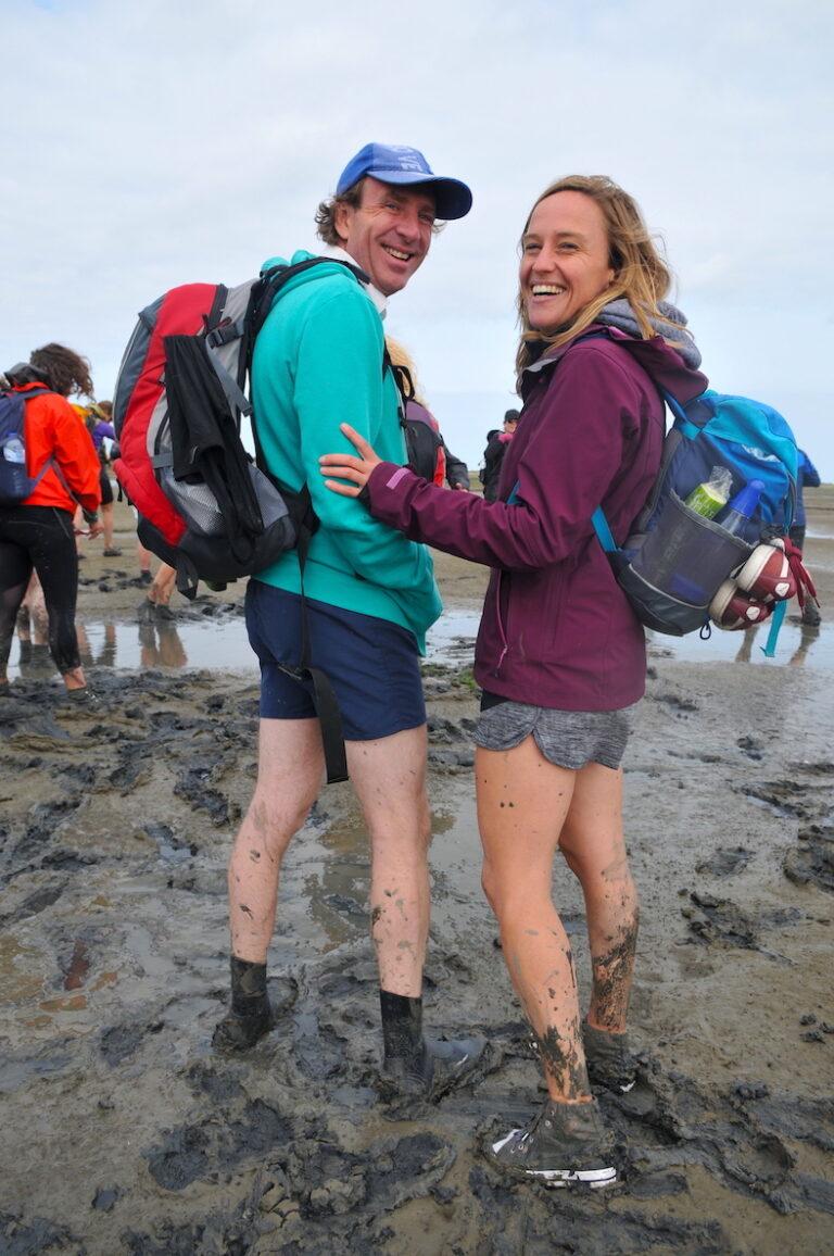 Two people in mud of Wadden Zee