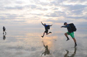 Man jumping in Wadden Sea mud